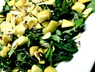 a pile of baby kale with diced mango, slivered almonds and dressing on top