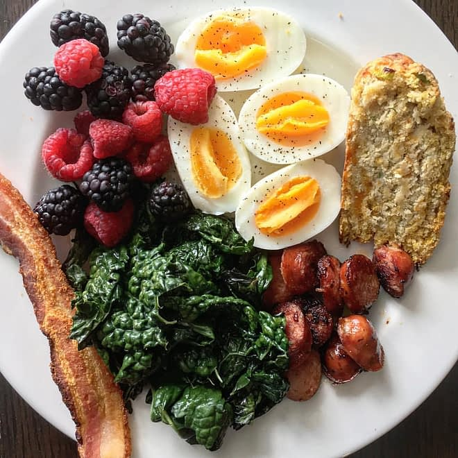 a breakfast plate with bacon, kale, berries, eggs, sausage and bread