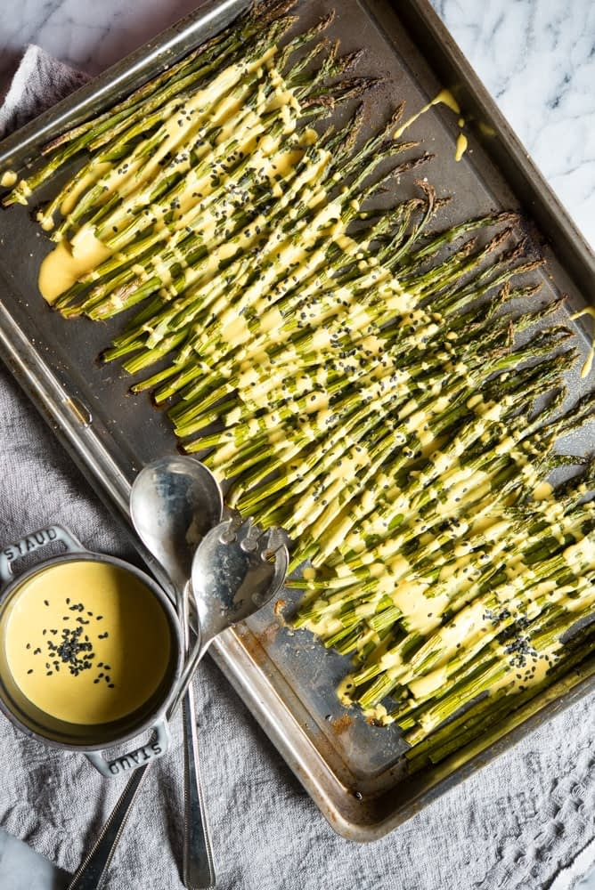 roasted asparagus on a metal baking sheet pan drizzled with yellow lemon cardamom cream sauce and sprinkled with black sesame seeds