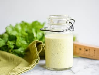 glass jar of cilantro hollandaise sauce on a white marble table with cilantro in the background