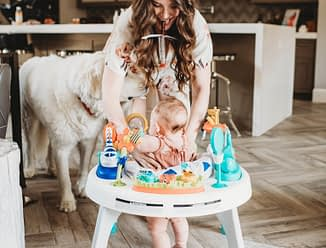 women with long dark hair standing over a baby in an activity chair eating a beef stick with a white dog in the background