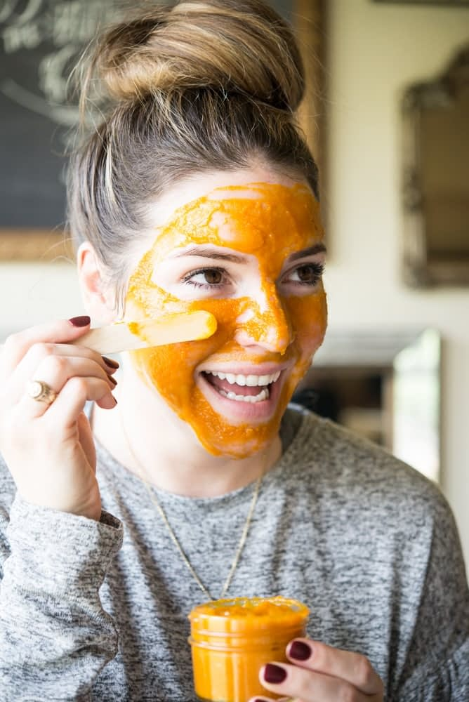 smiling woman with a bun and applying a DIY pumpkin facial mask