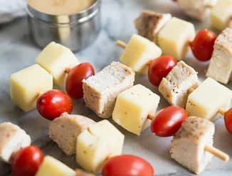 overhead view multiple chicken skewers with cheese and tomatoes and honey mustard dipping sauce