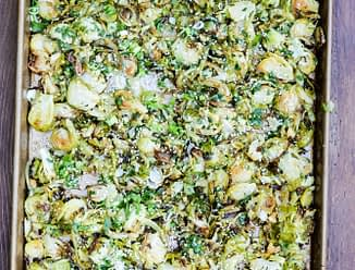 overhead view of a sheet pan of shaved Brussel sprouts on a wood table