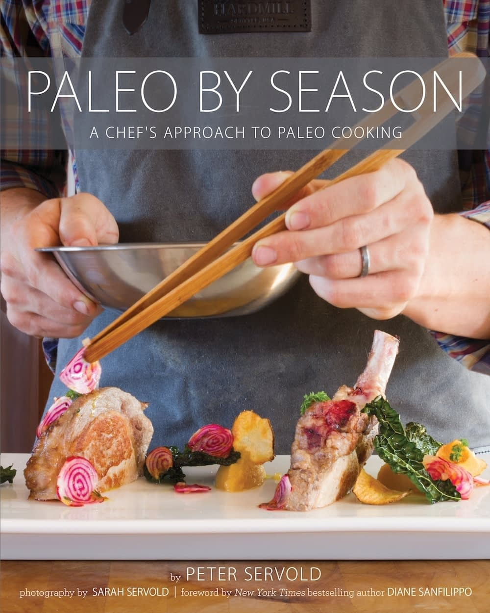 Paleo by Season book cover with an image of a mans hand holding a bowl and a pair of tongs and adding watermelon radishes as a garnish to lamb chops