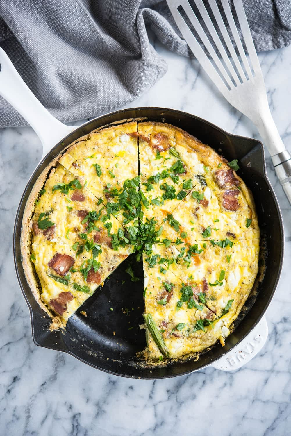goat cheese and veggie frittata in a cast iron pan on a marble board with a grey napkin