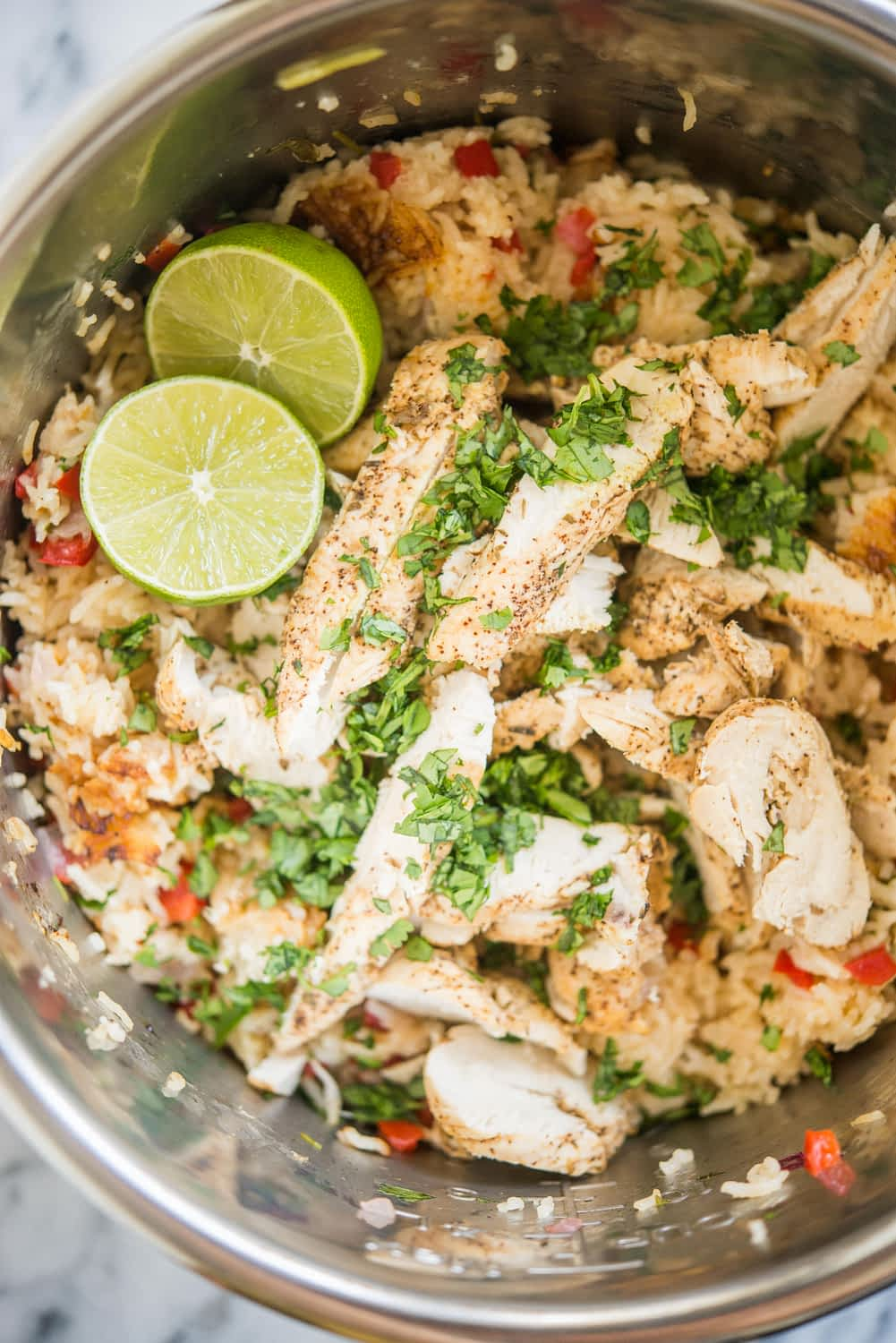 instant pot chicken fajitas and rice in a metal pot garnished with limes and chopped cilantro