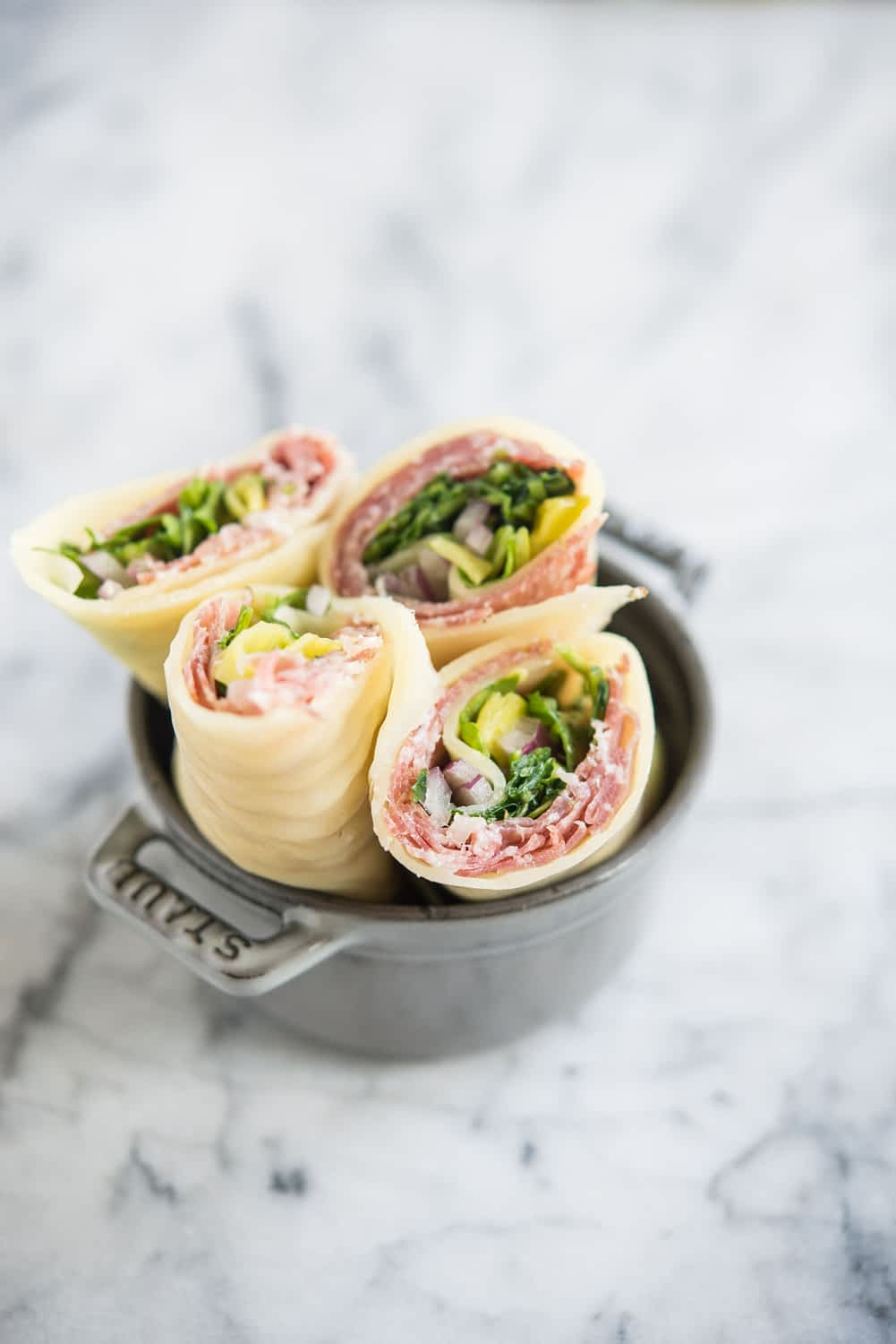 Keto Lunch wraps with Italian meats, arugula, pepperoncini, and red onion, cut in half in a small grey bowl on a marble board