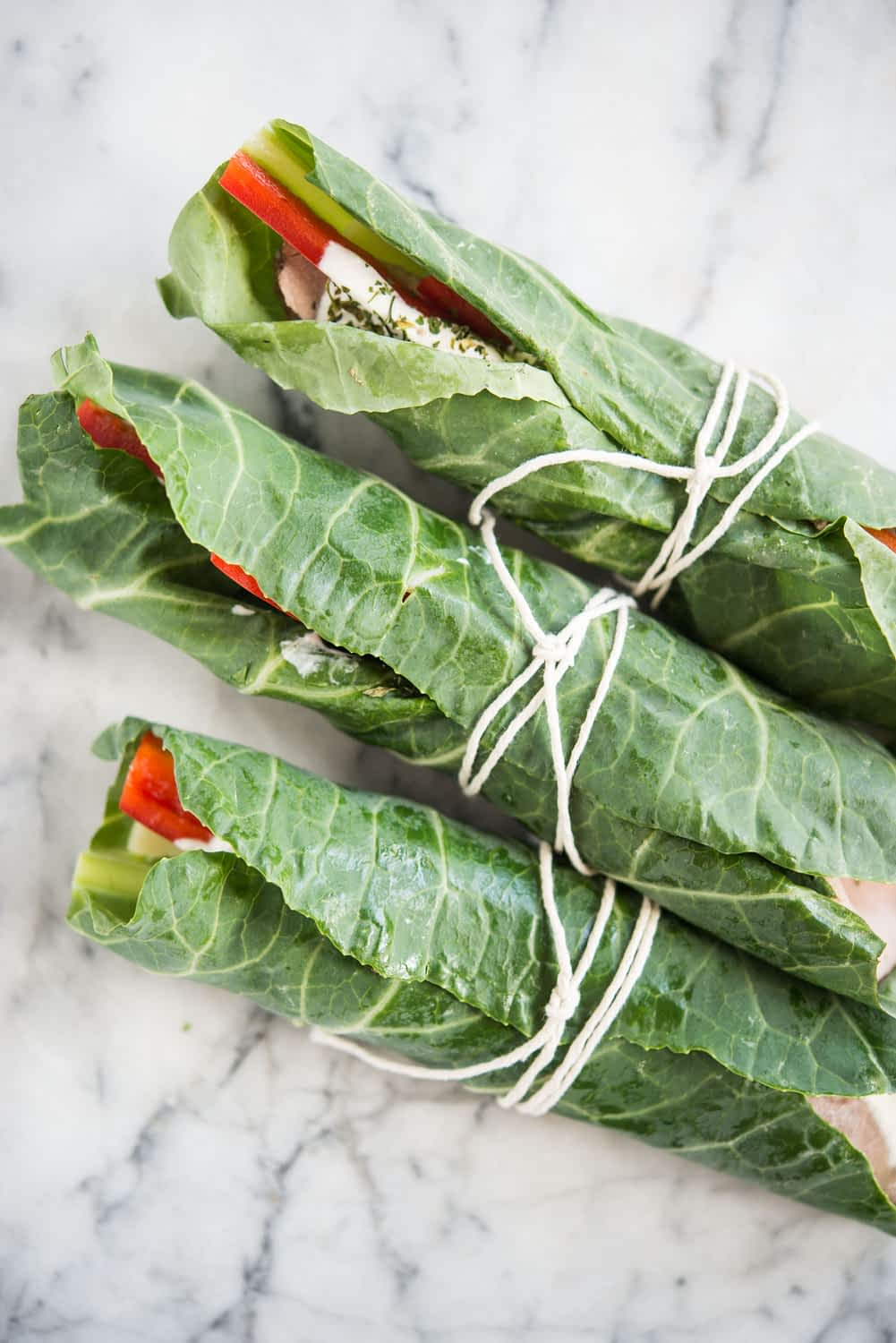 3 roast beef wraps in collard green leaves rolled up and tied with string on a marble board