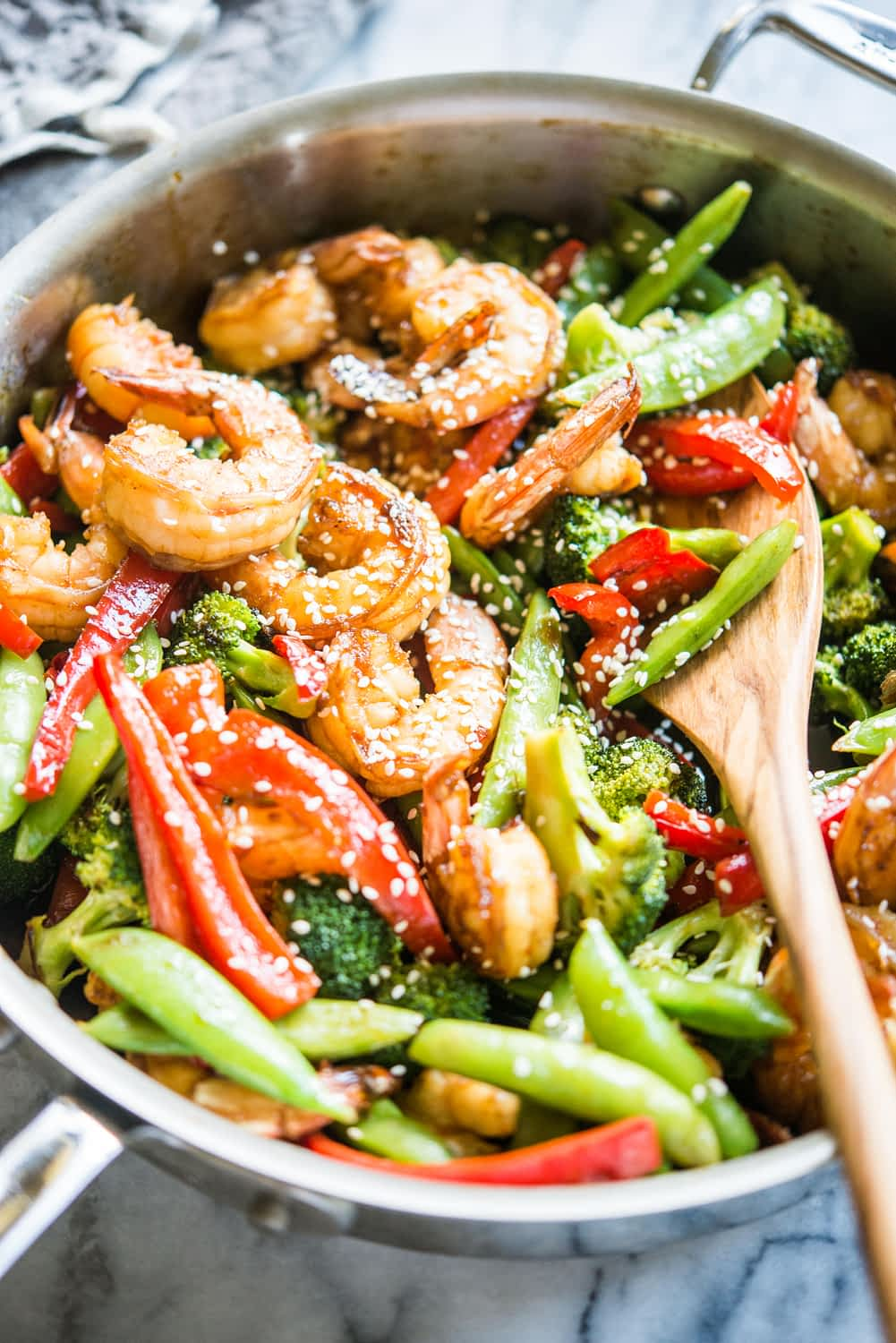 teriyaki shrimp stir fry with shrimp, red bell peppers, broccoli, and snap peas in a stainless steel skillet on a marble countertop