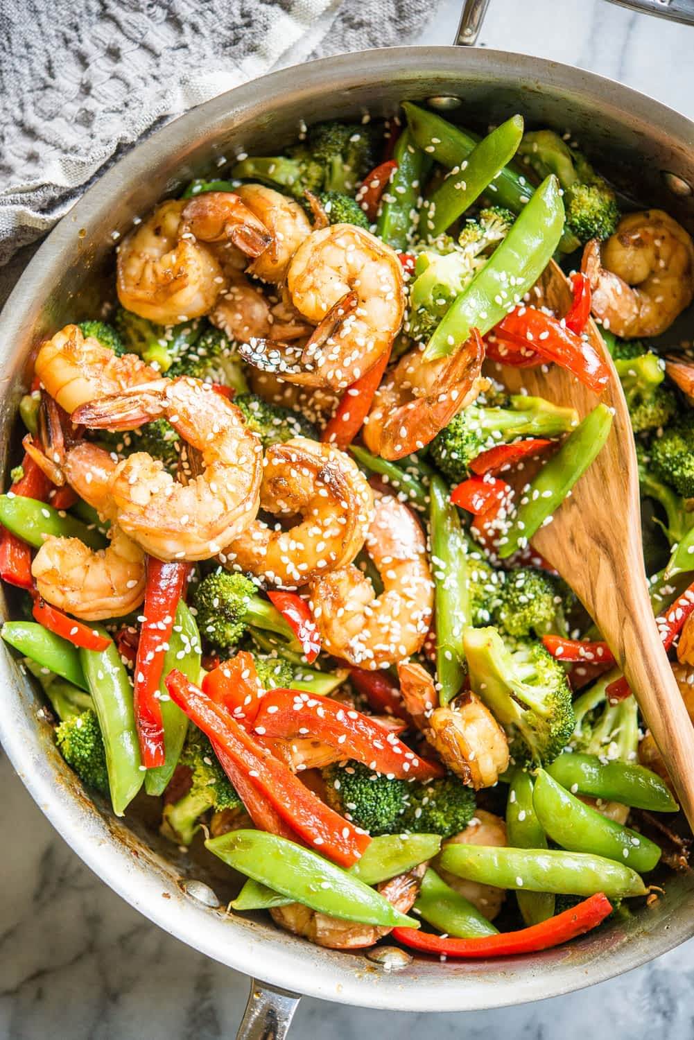 teriyaki shrimp, bell peppers, broccoli, and snow peas in a stainless steel skillet on a marble board