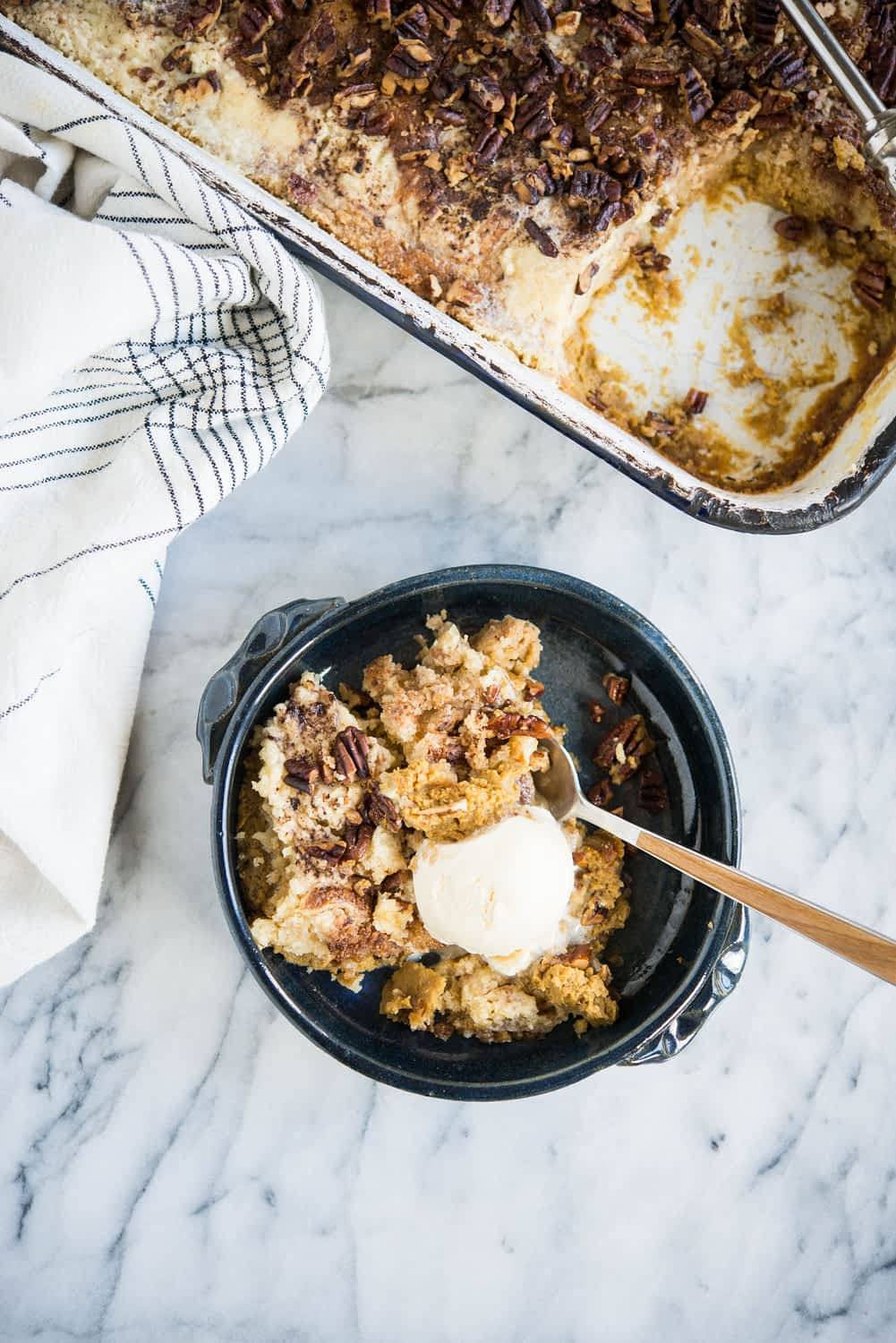 pumpkin pie dump cake in a dark blue bowl with a scoop of ice cream on top