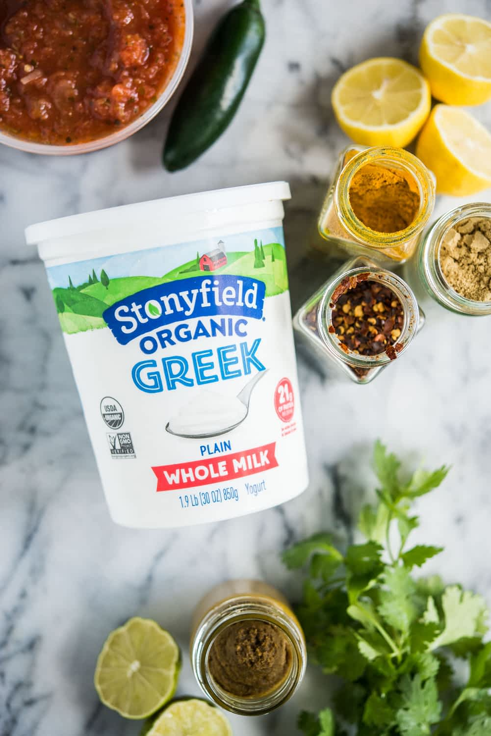 a container of stonyfield greek yogurt on a marble board surrounded by spices, lemons, limes, and salsa