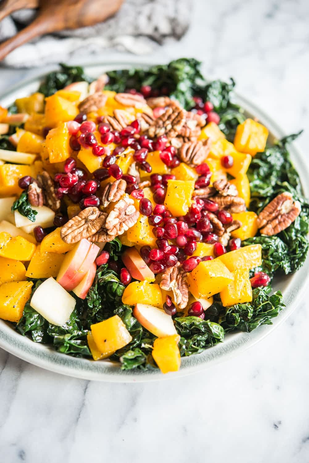 kale salad with roasted butternut squash, pecans, apples, and pomegranate seeds on a gray plate on a marble board