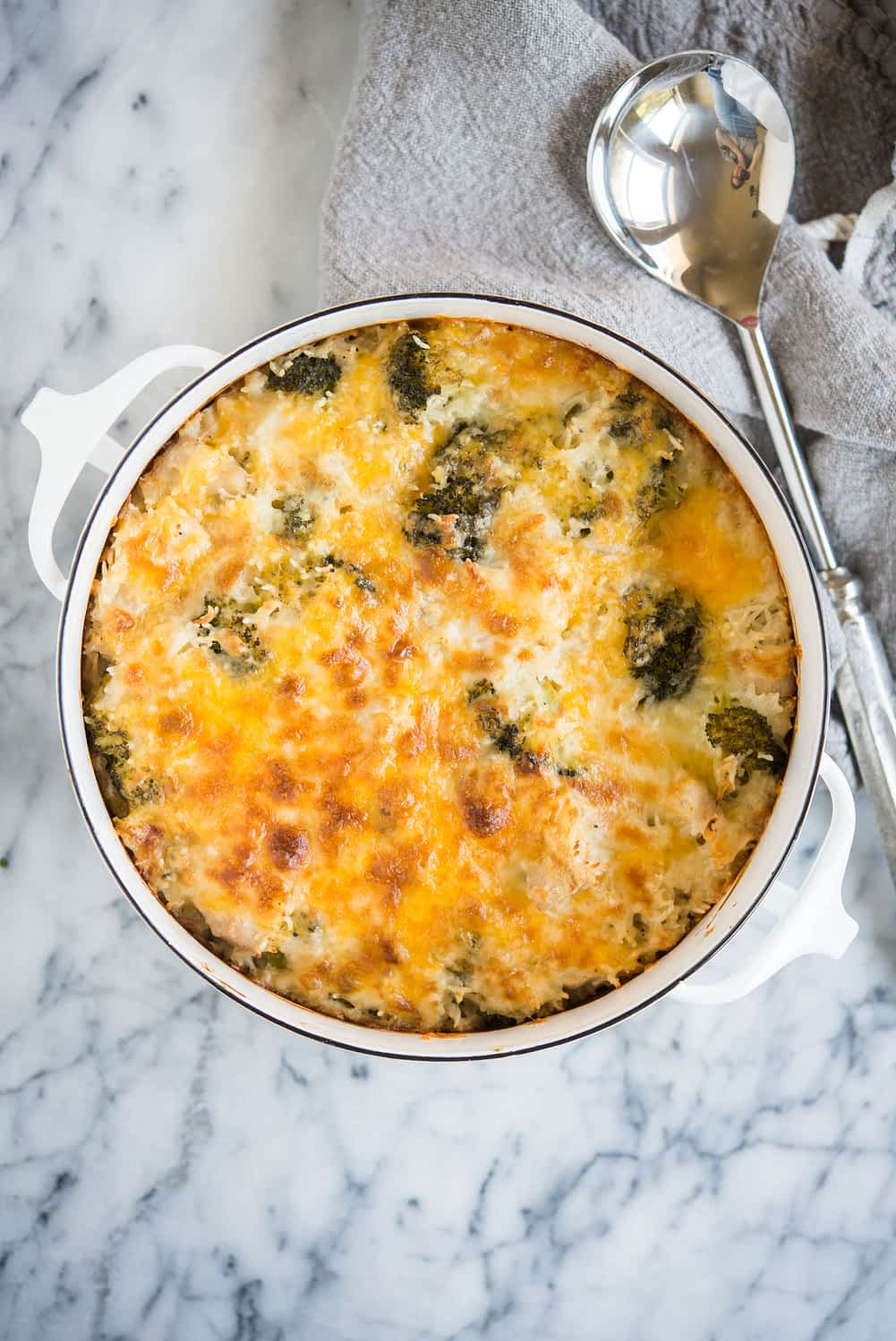 chicken broccoli and rice casserole with cheese in a white casserole dish on a marble surface