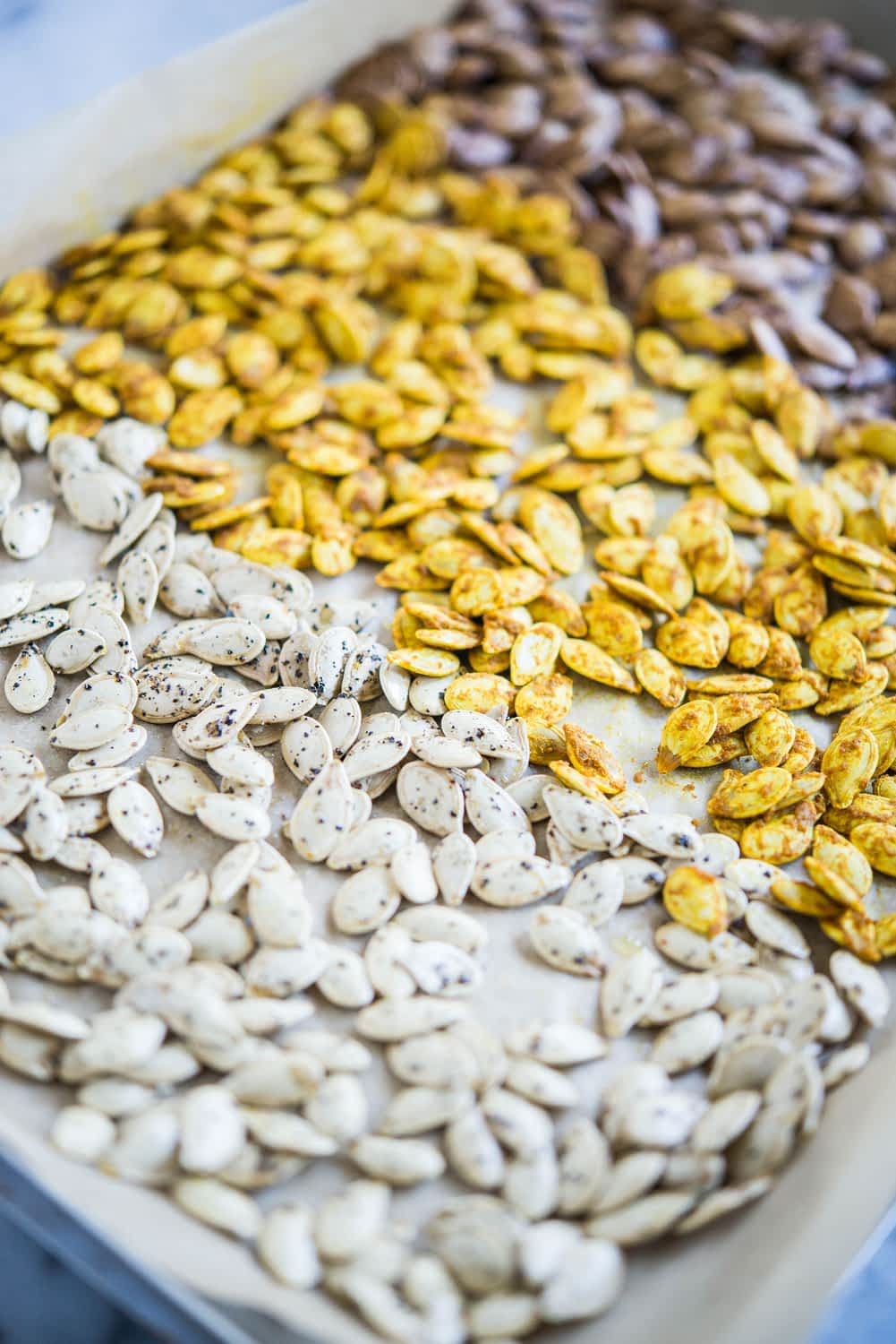 3 flavors of homemade pumpkin seeds, one white, one bright yellow, and one dark brown, on a sheet of parchment paper