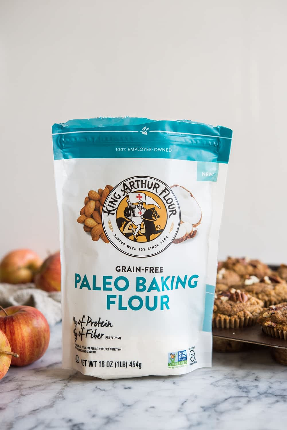 a bag of king arthur paleo baking flour on a marble board with muffins and apples in the background