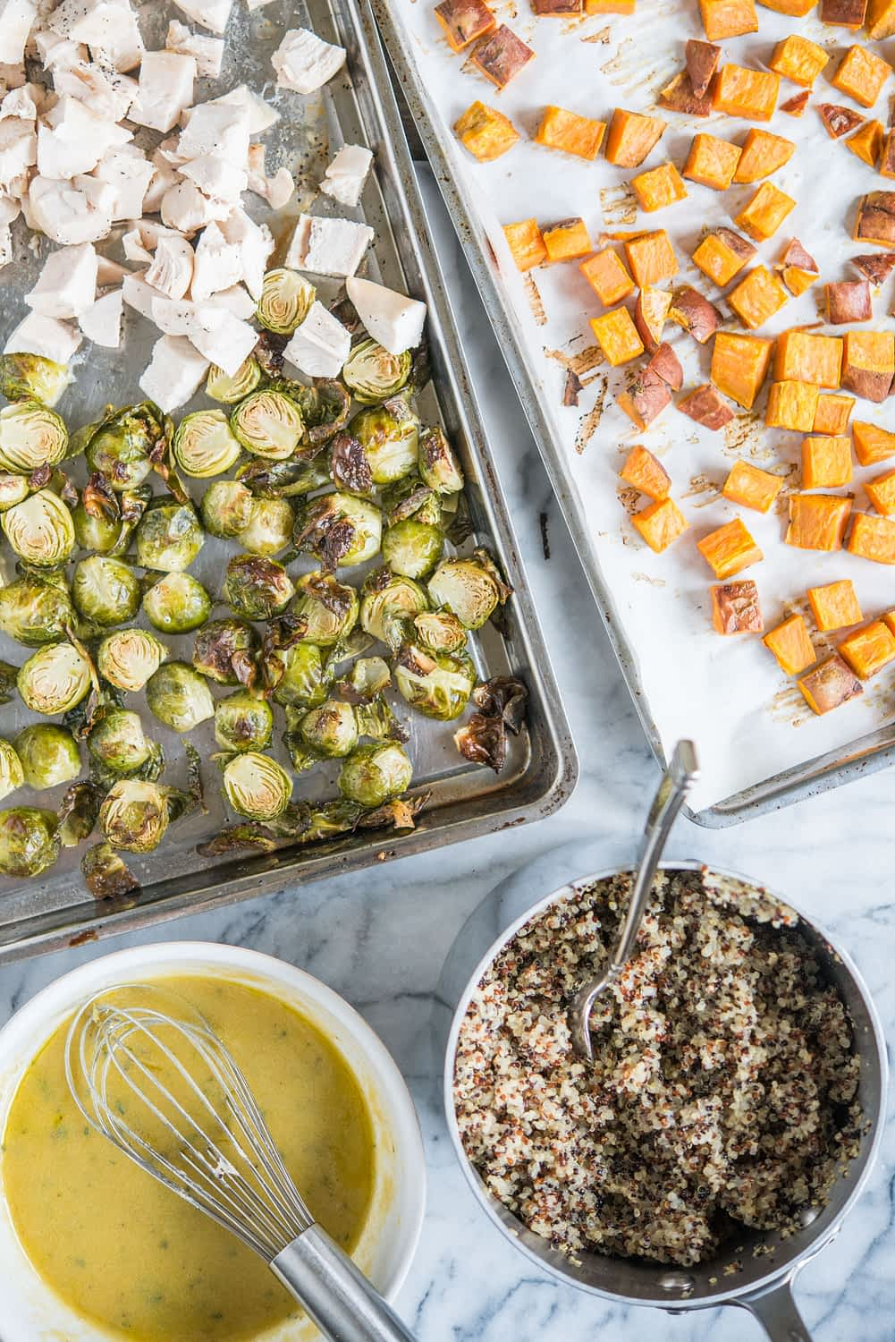cubed chicken breast, roasted brussels sprouts, and roasted sweet potatoes on two sheet pans next to a pot of quinoa and a bowl full of dijon dressing
