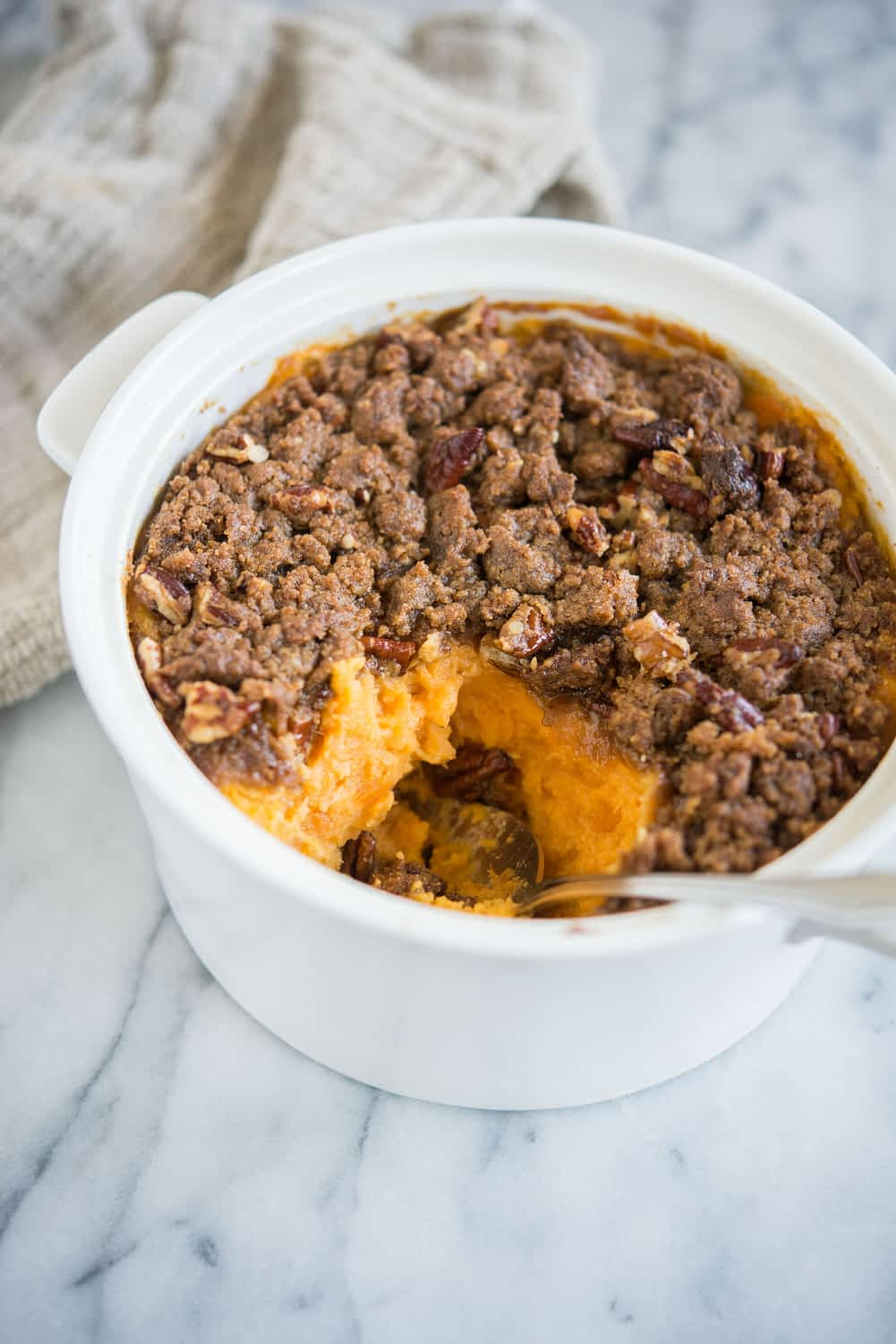 sweet potato casserole with pecan topping in a white casserole dish with a scoop taken out of it sitting on a marble surface