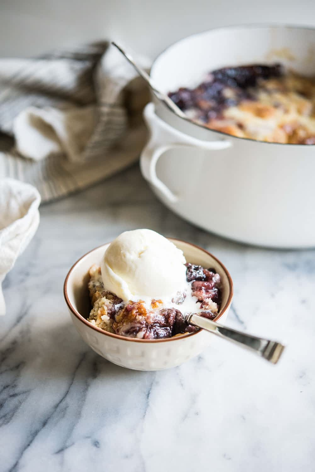 cherry dump cake in a white bowl with a scoop of ice cream on top