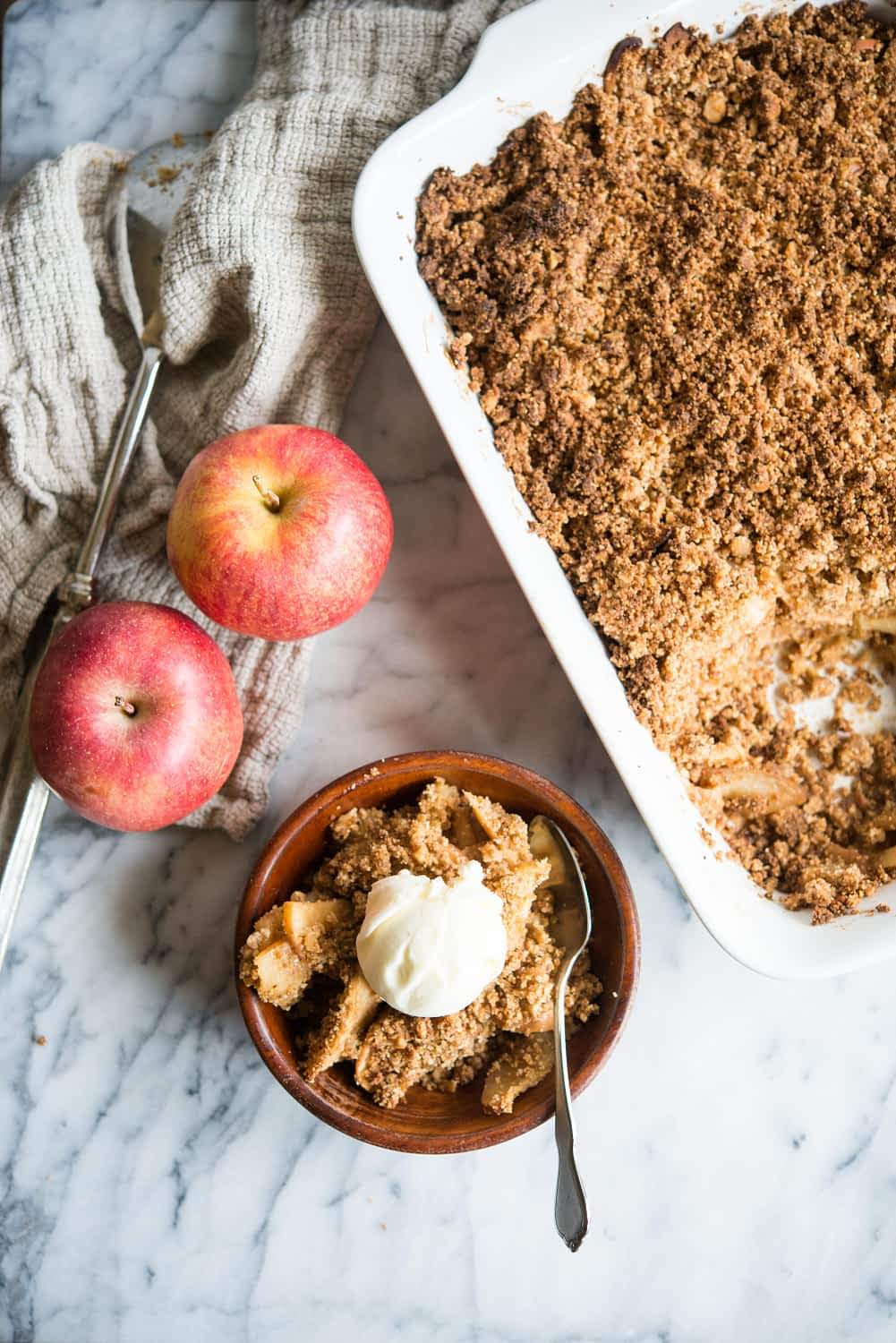 paleo apple crisp in a white rectangular dish with some spooned out into a wooden bowl and topped with a scoop of ice cream