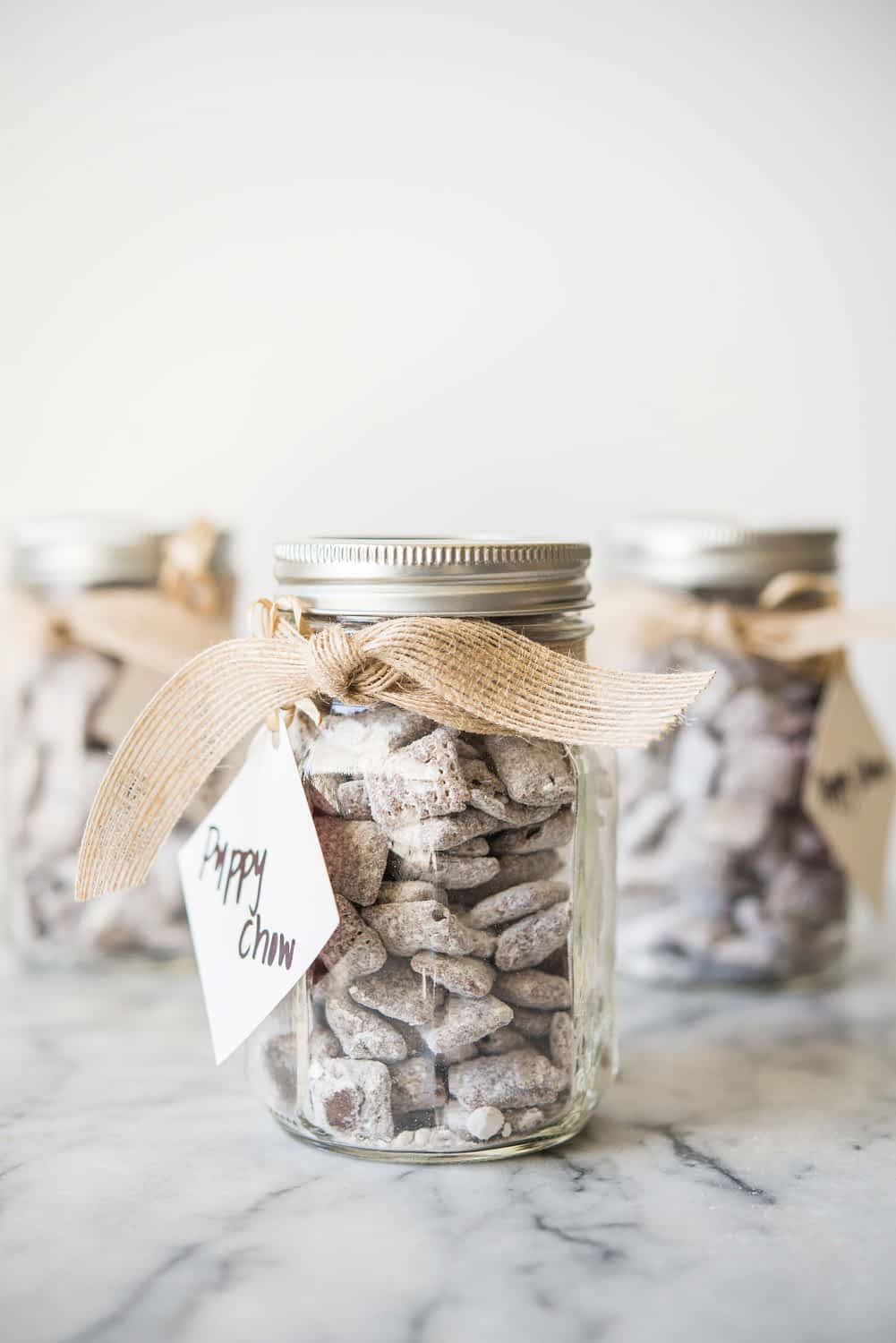 puppy chow in a mason jar with a bow tied around it and a gift tag that says 'puppy chow'