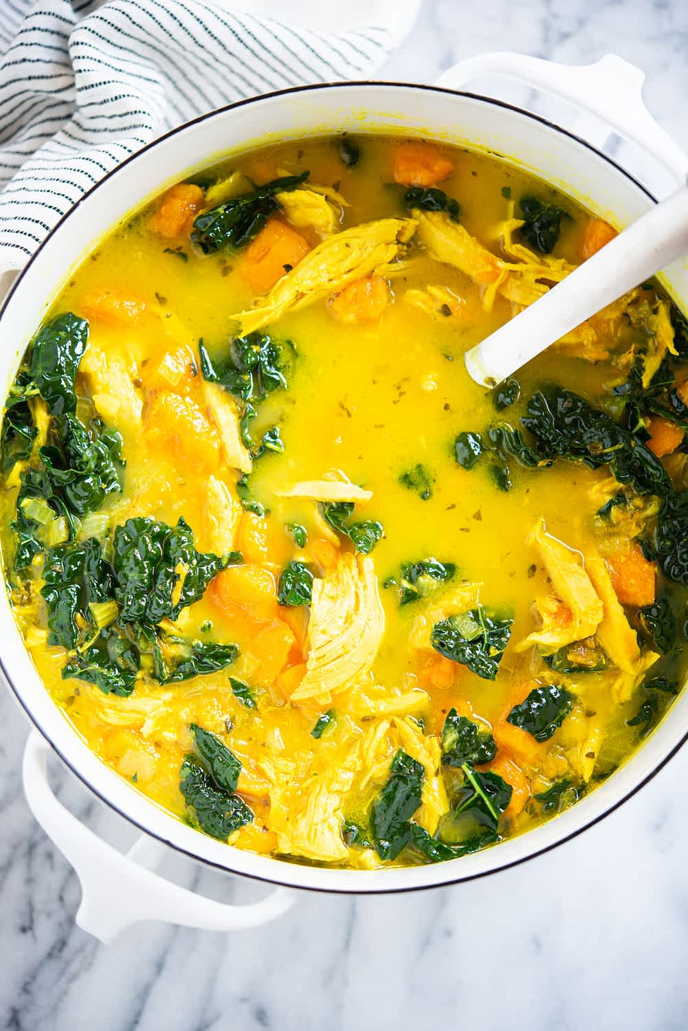 healing chicken soup with yellow turmeric broth, sweet potatoes, and kale in a white pot on a marble surface