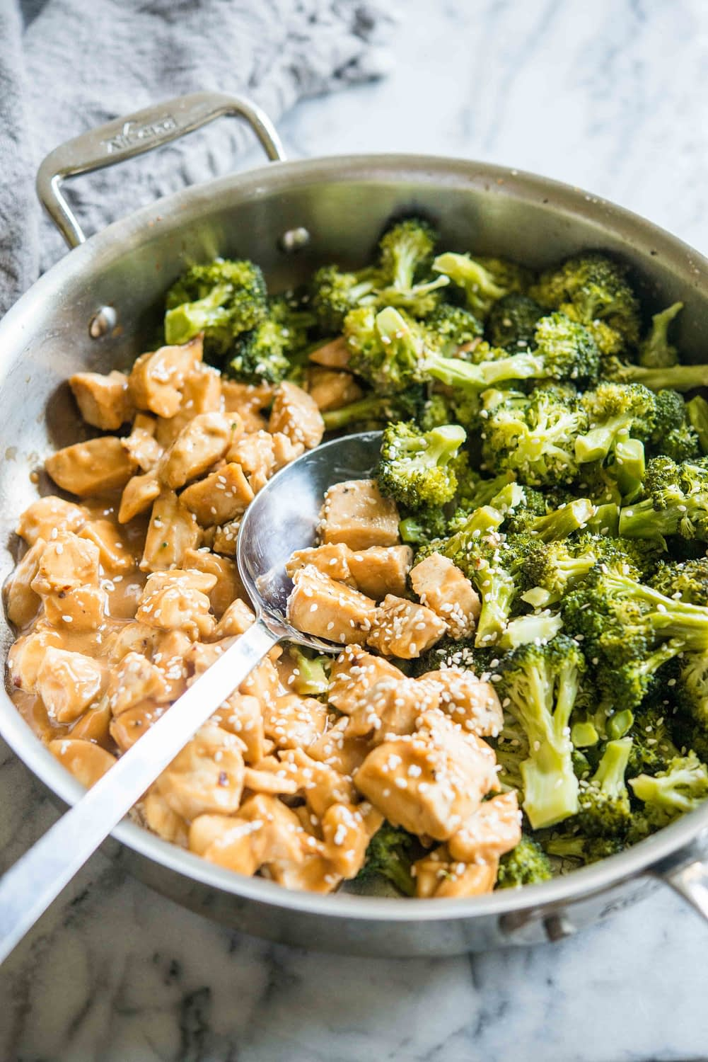 chicken with peanut sauce in a pan with broccoli on a marble board