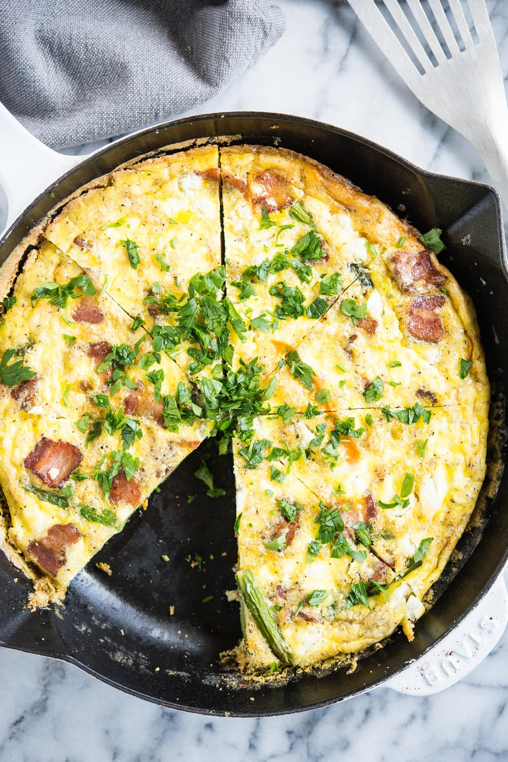 frittata with asparagus, goat cheese, and bacon in a cast iron pan with one slice missing on a marble board