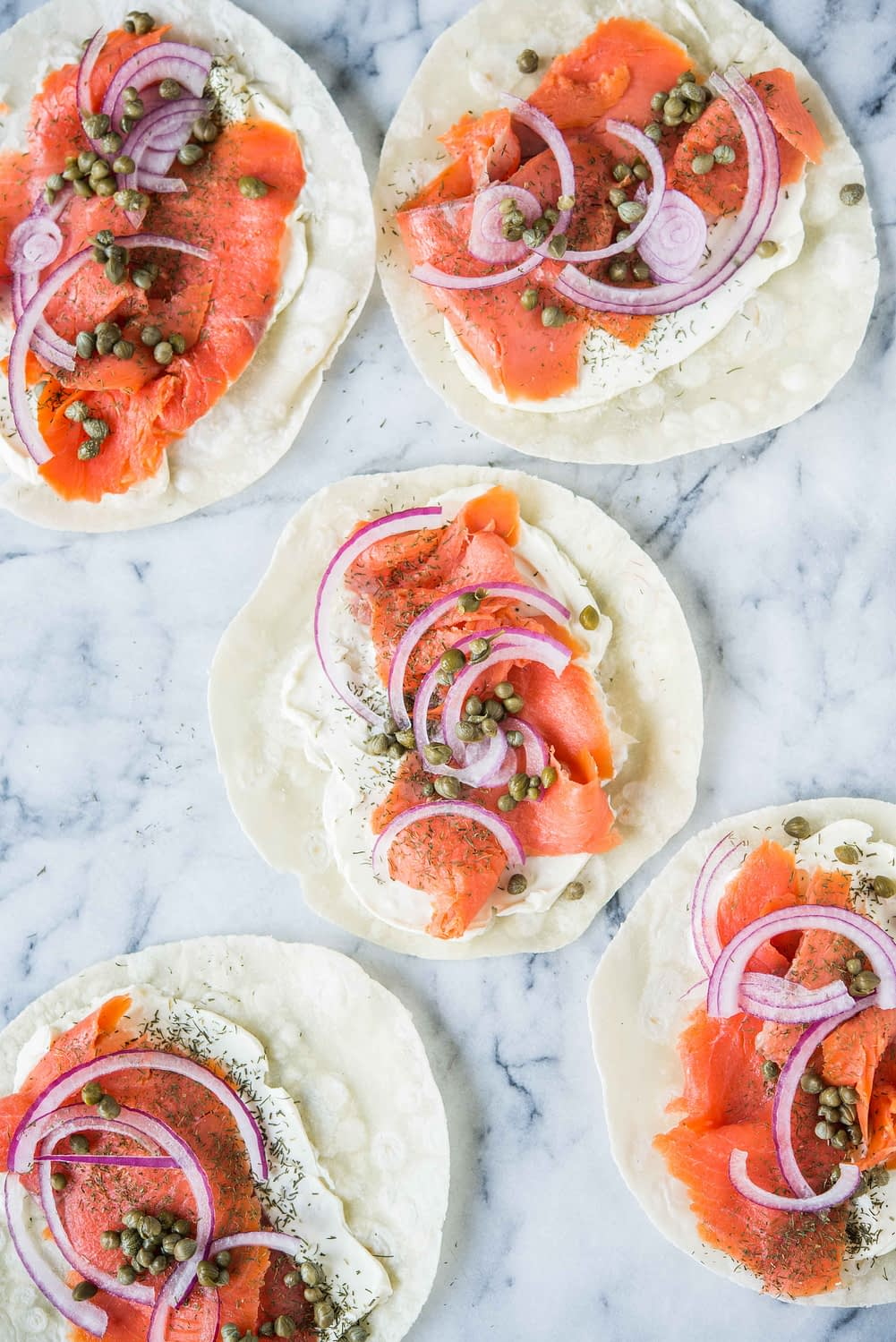 tortillas smeared with cream cheese, smoked salmon, capers, and red onion, on a marble board