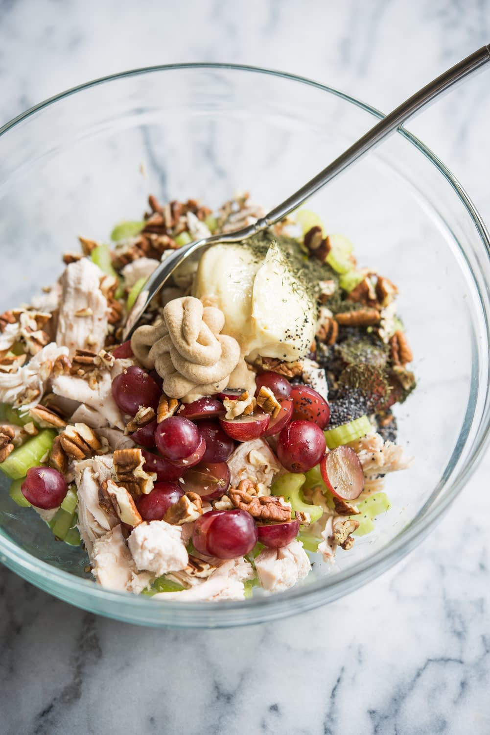 chicken, grapes, pecans, celery, mayo, and mustard in a glass bowl on a marble board