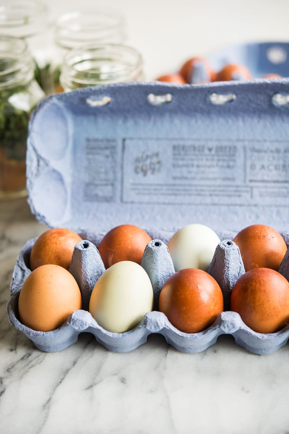 blue and brown eggs in an egg carton on a marble board