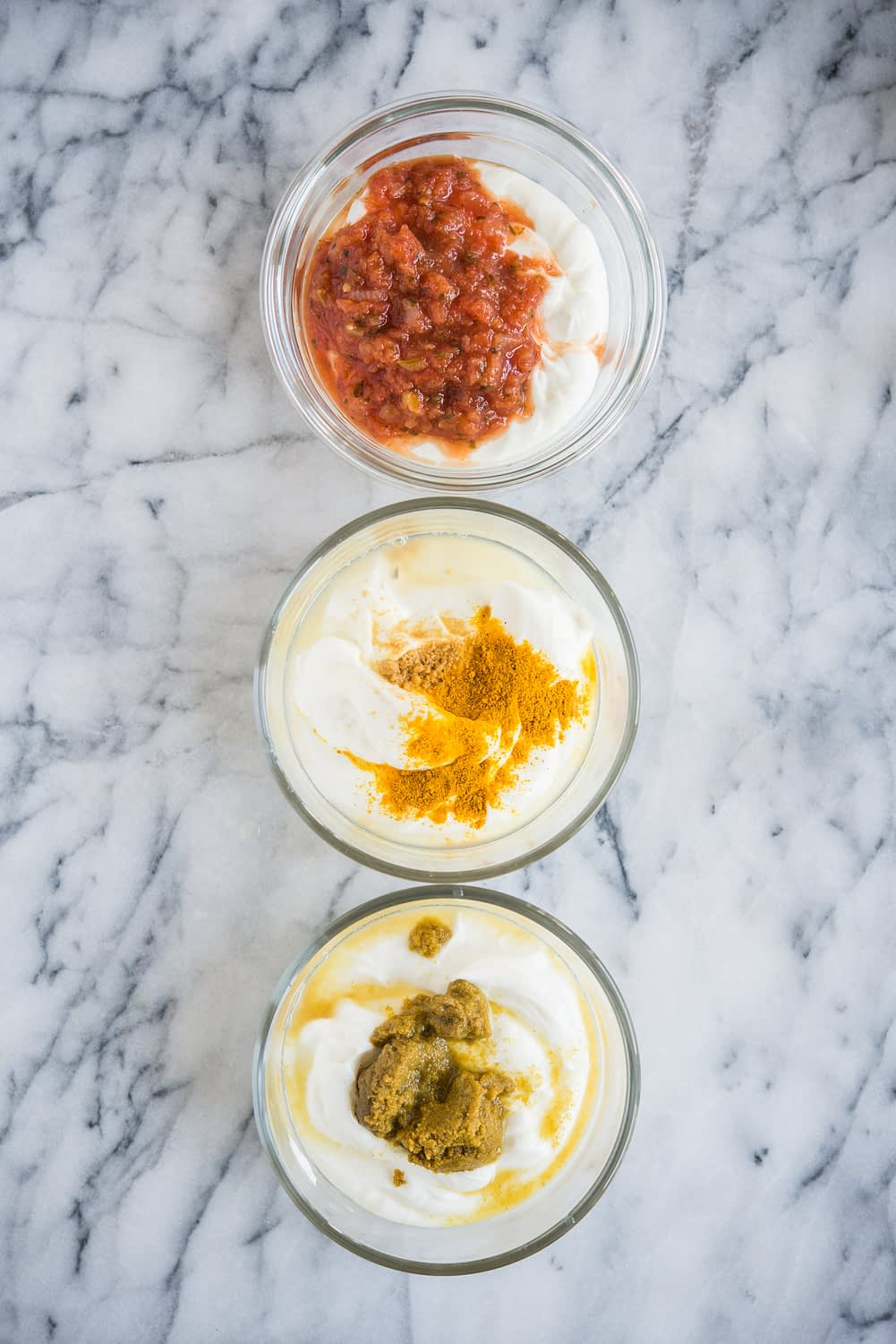 three bowls of greek yogurt lined up with spices on top sitting on a marble counter