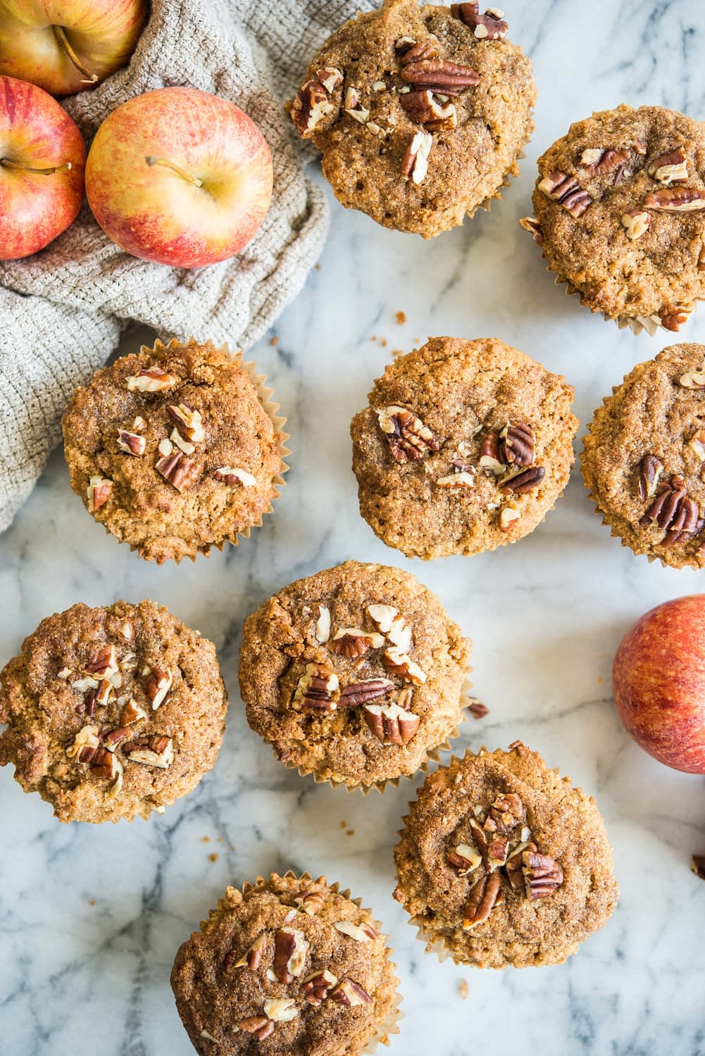 paleo apple cinnamon muffins on a marble board surrounded by apples