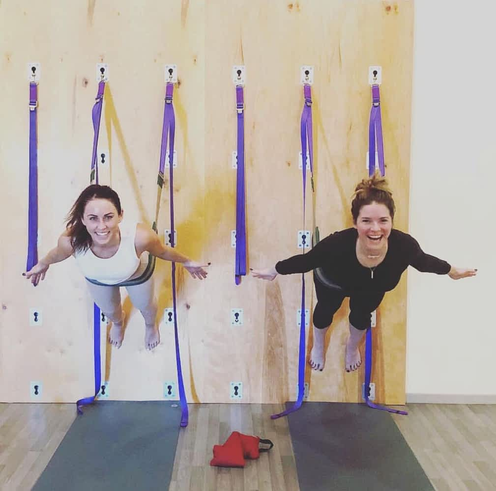 two smiling women doing an aerial fitness class at a wellness retreat in phoenix