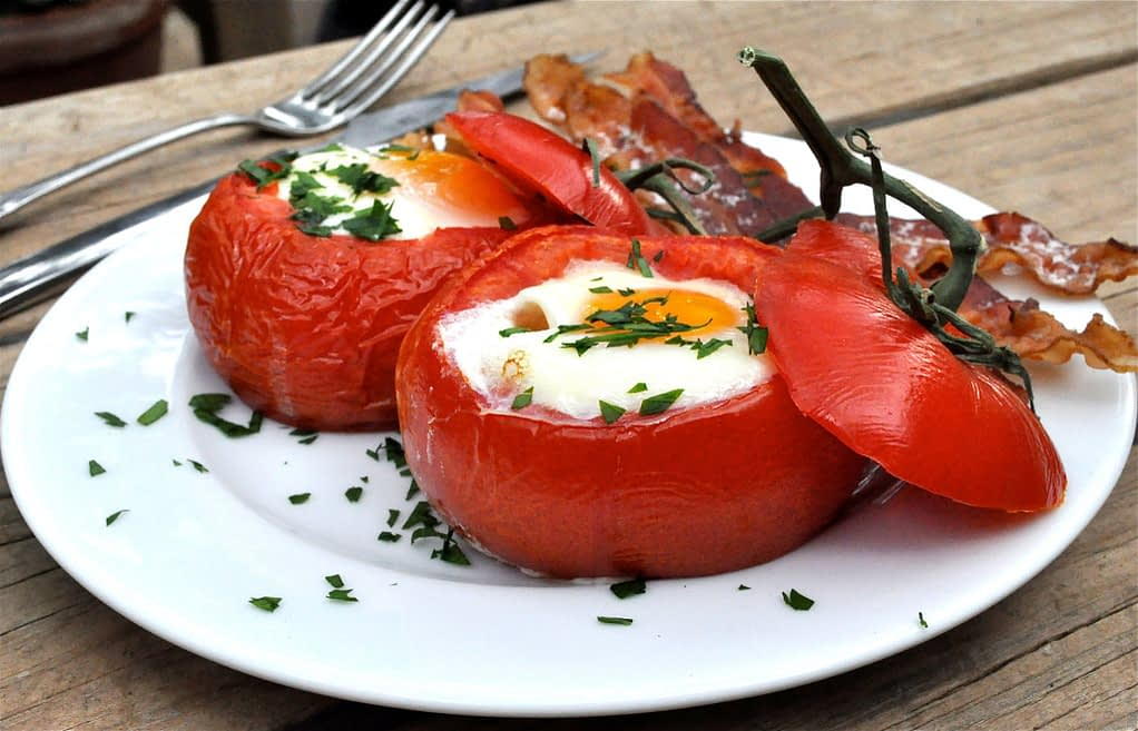 a white plate with two baked tomato eggs on top