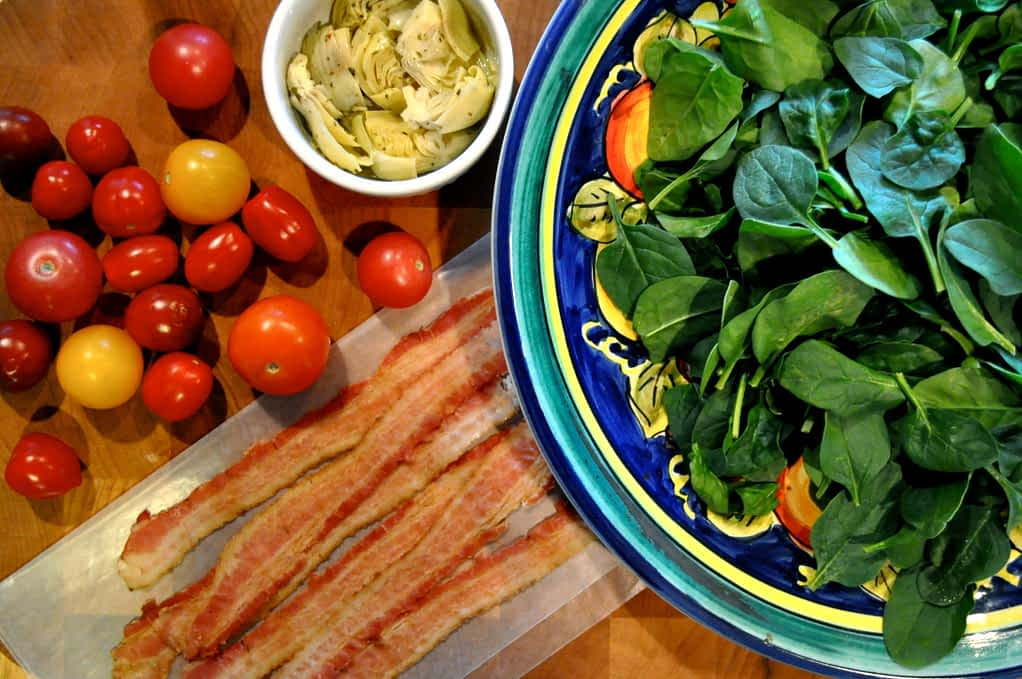 overhead view of a plate of spinach, bowl of artichokes, and cherry tomatoes