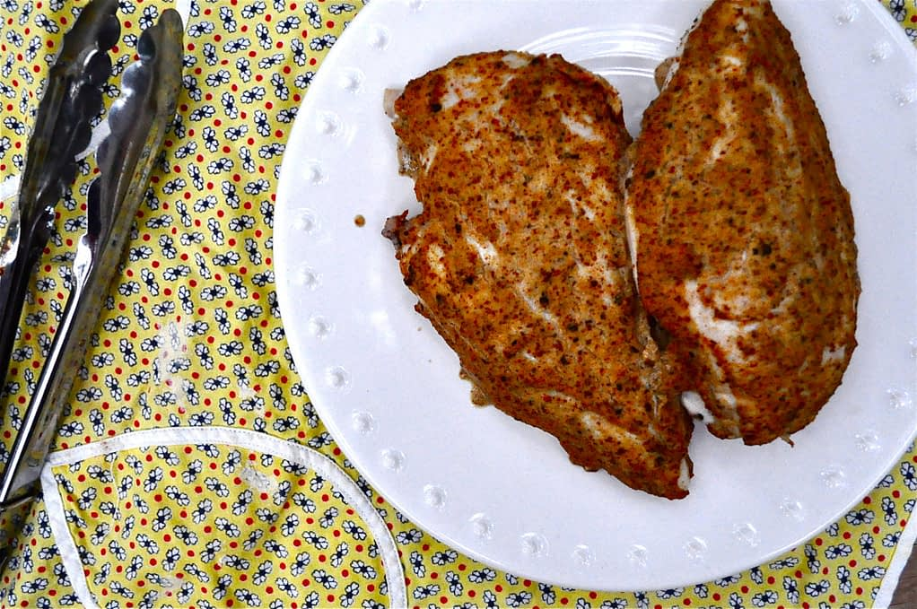 overhead view of two baked mustard chicken breasts on a white plate on top of a yellow flower patterned napkin
