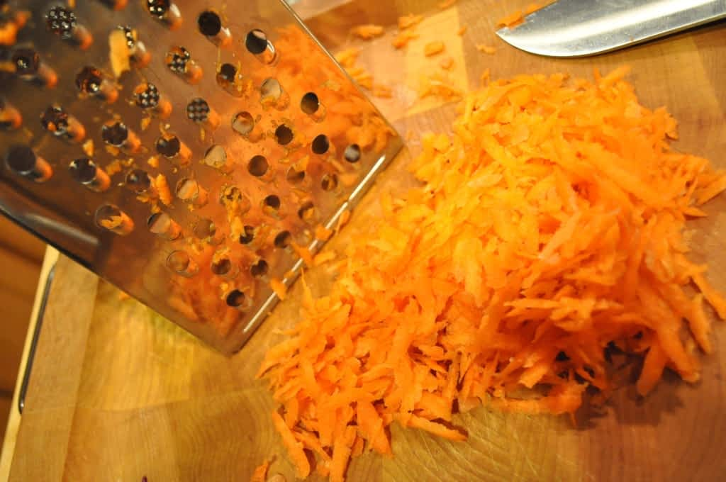 a cheese grater with a pile of shredded carrots