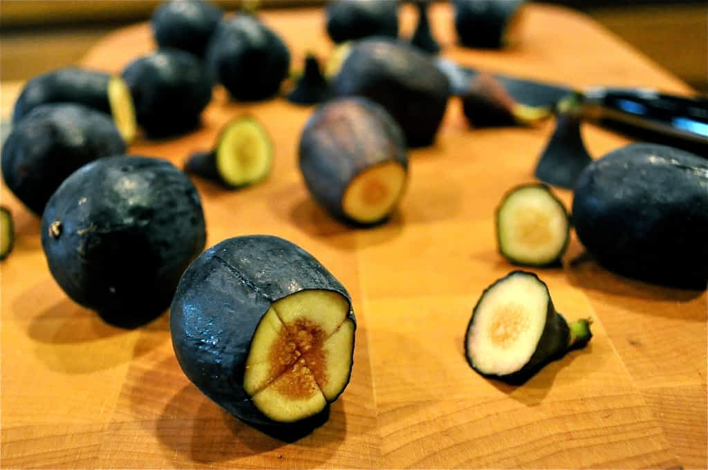 fresh figs on a cutting board with one end cut off and an X cut in the middle