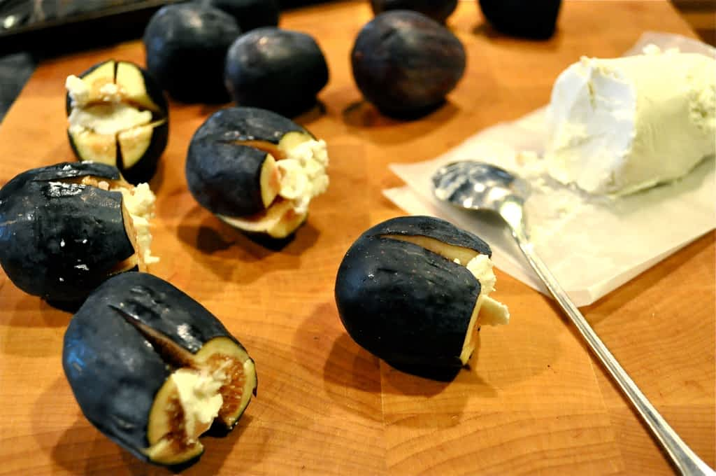 fresh figs stuffed with goat cheese on a cutting board