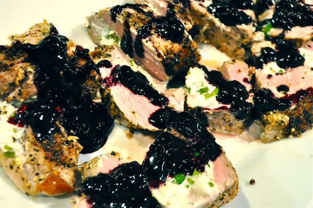 blueberry reduction drizzled on top of sliced pork chops
