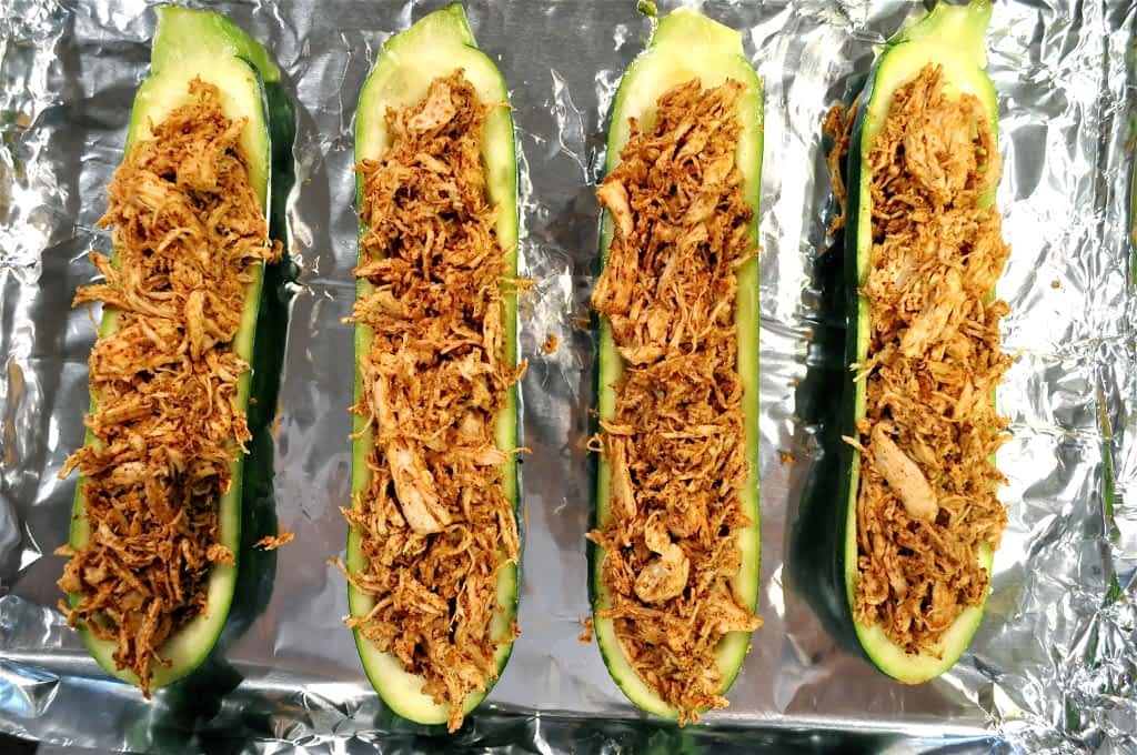 overhead view of hollowed out zucchini halves stuffed with shredded chicken and spices on a foil lined baking sheet