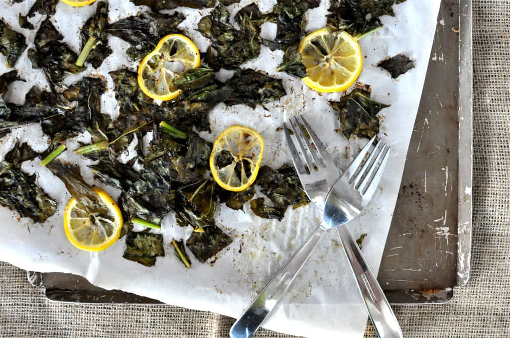 overhead view of charred turnip greens and lemon slices on parchment paper and a sheet pan