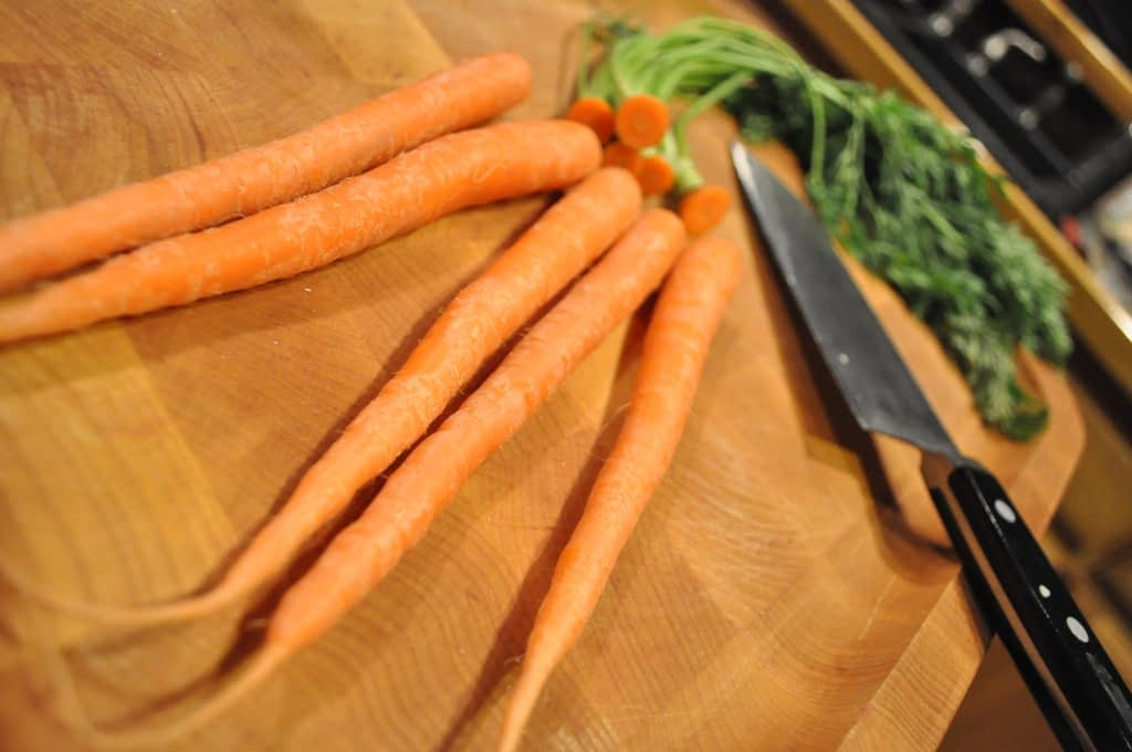 carrots on a wooden cutting board with a knife