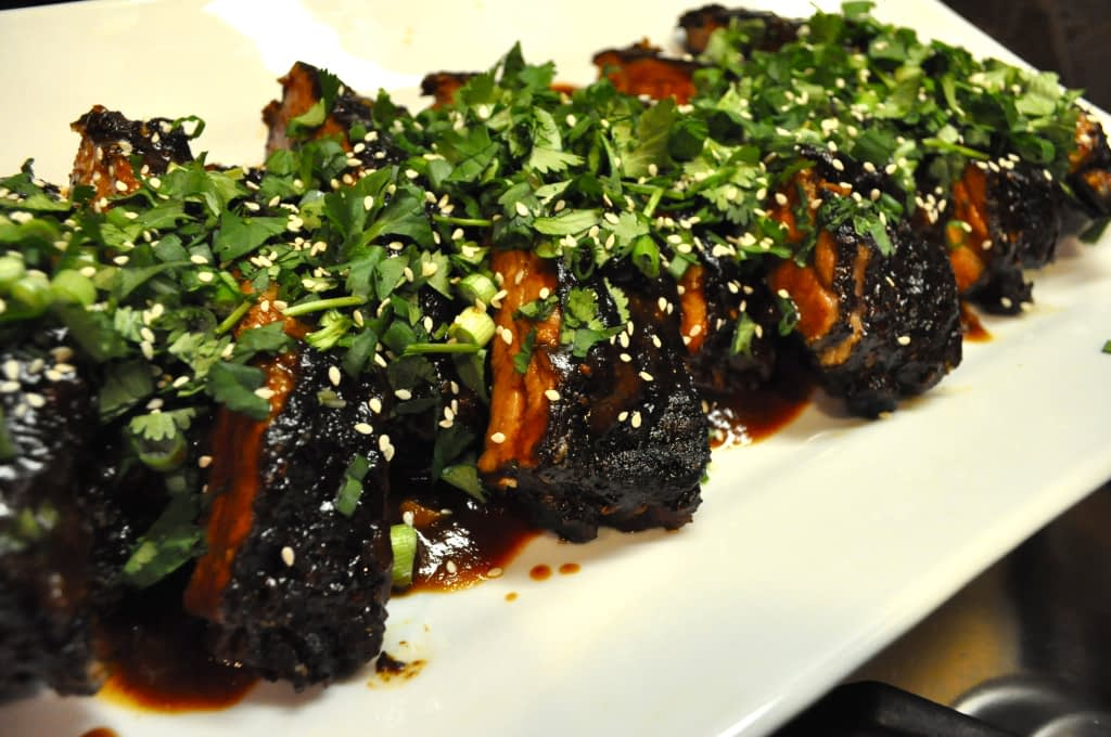 a white platter of Chinese short braised ribs topped with cilantro and sesame seeds