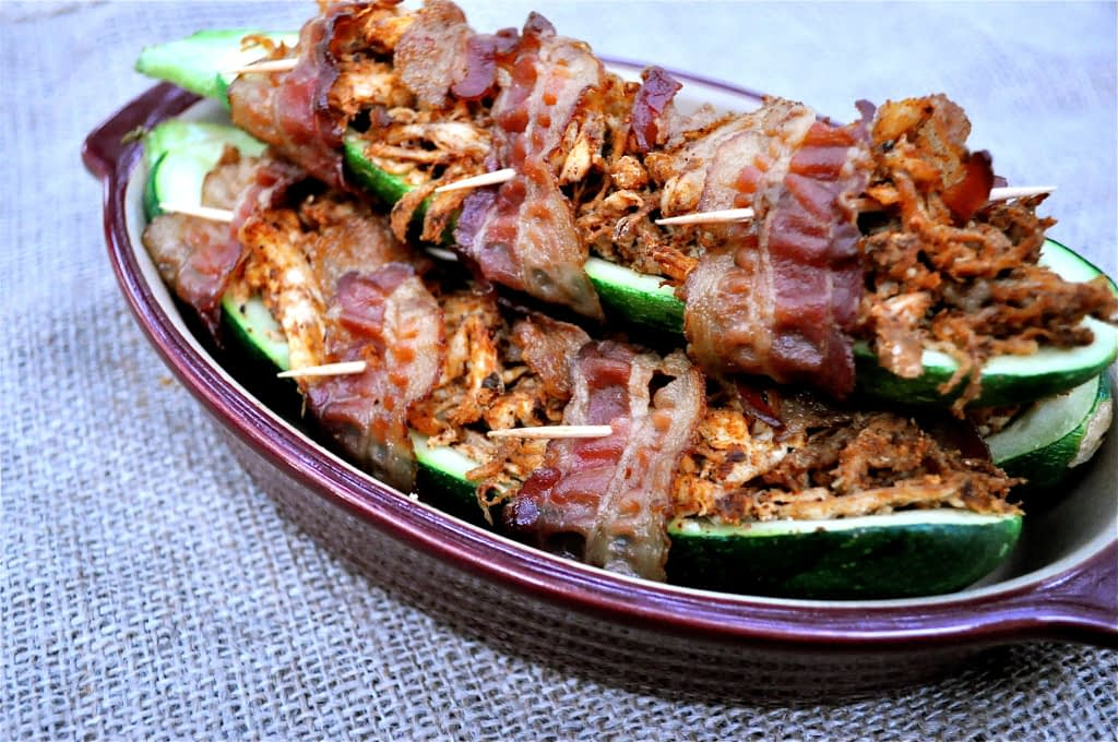 bacon wrapped stuffed zucchinis in a red casserole dish on top of a burlap covered table