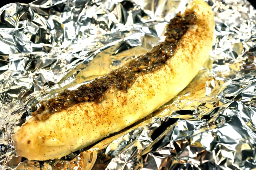a peeled banana topped with almond butter sitting in foil