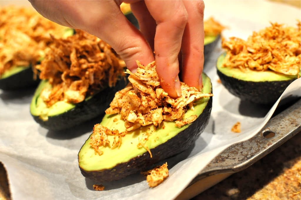 Shredded chicken being stuffed into avocados