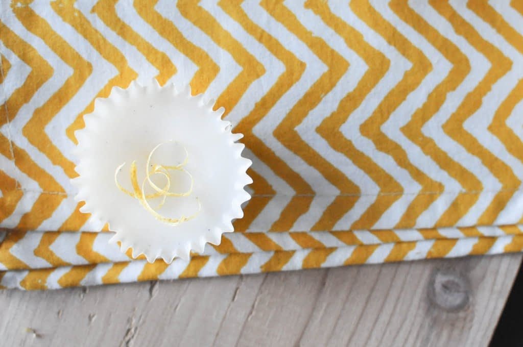 overhead view of one white lemon vanilla beltway topped with lemon zest and placed on a yellow zig zag napkin